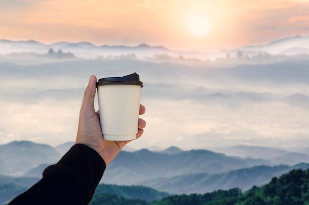 흐림 산 풍경과 뜨거운 커피 종이 컵을 들고 남자 손