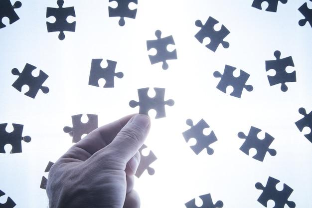 ジグソーパズルを持っている男性の手。 Premium写真