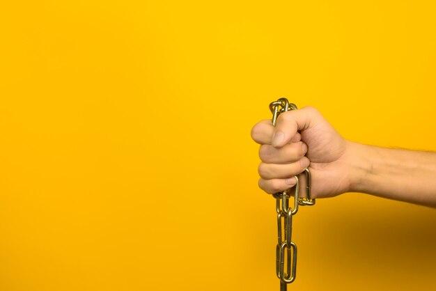 屋内で黄色の背景に金属チェーンを持っている男性の手。スペースをコピーします。