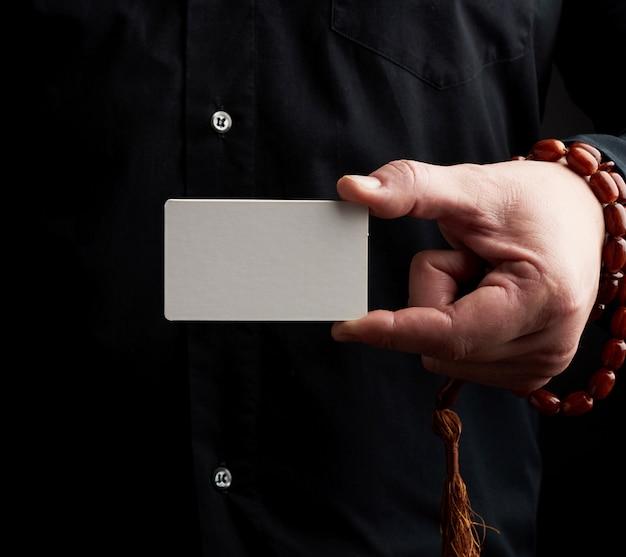 Мужской рукой, держащей прямоугольную пустую белую визитку