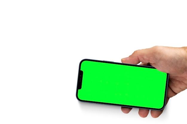 녹색 화면이 있는 스마트폰을 들고 있는 남성 손. 크로마 키. 흰색 배경에 고립.