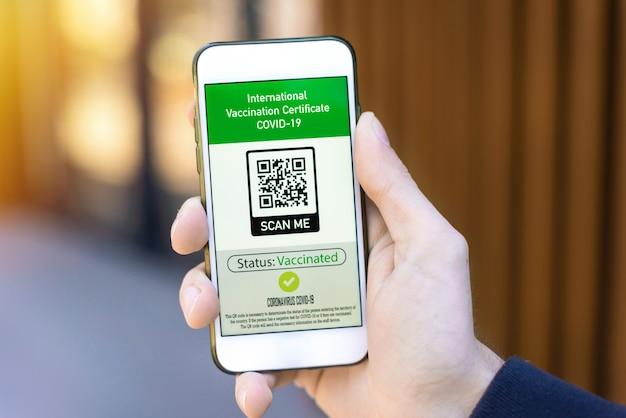 国際予防接種証明書covid-19 qrコードが付いたスマートフォンを持つ男性の手