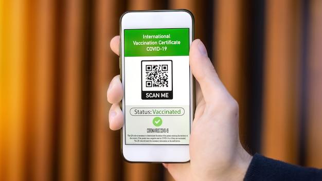 国際予防接種証明書covid19 qrコード付きのスマートフォンを持つ男性の手
