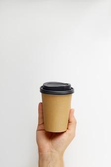 흰색 배경에 고립 된 테이크 아웃 커피 종이 컵을 들고 남성 손