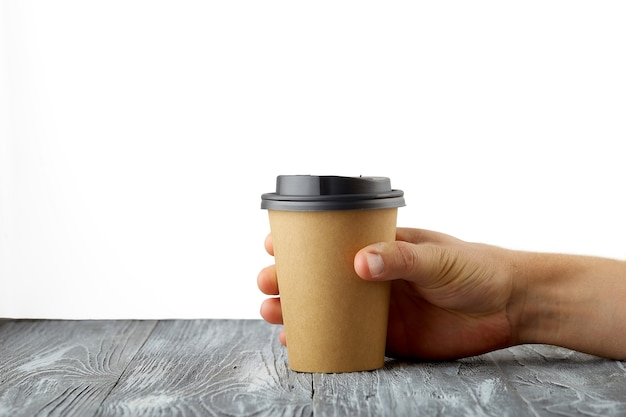 회색 나무 배경에 테이크 아웃 커피 종이 컵을 들고 남성 손