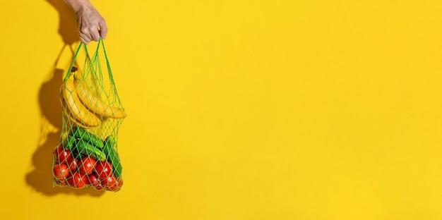 コピースペースと黄色の背景に野菜と白いメッシュバッグを持っている男性の手。ゼロウェイストショッピングコンセプト。