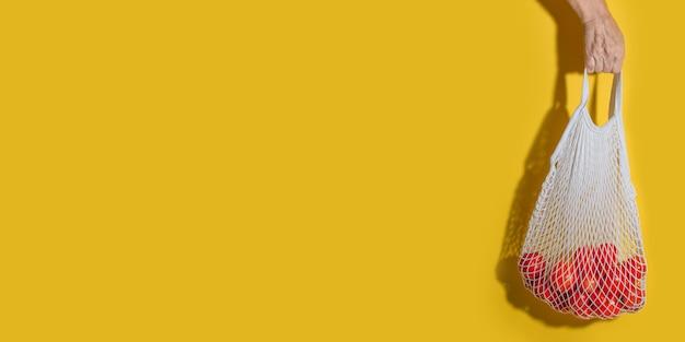 コピースペースと黄色の壁に野菜と白いメッシュバッグを持っている男性の手。ゼロウェイストショッピングコンセプト。トマトのストリングショッピングバッグ。プラスチックの拒絶。