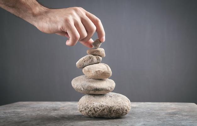 Male hand holding balance stone.