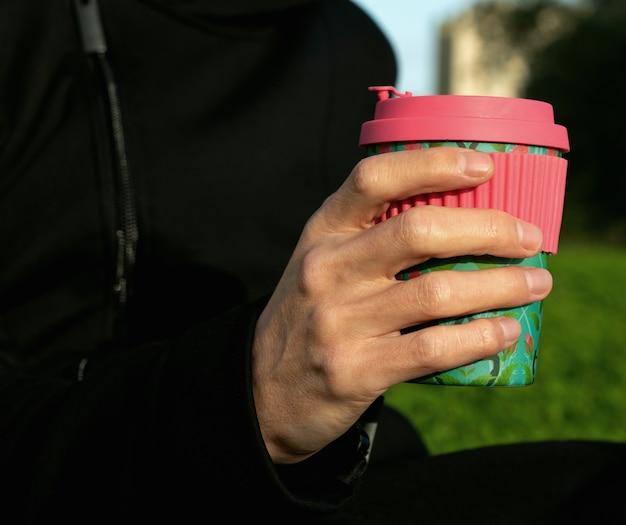 コーヒーの竹カップを持っている男性の手。公園でコーヒーを飲む。持続可能性の概念。テイクアウトドリンク