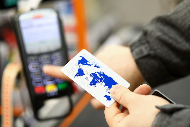 Male hand holding banking card while paying with it at cash desk of supermarket close-up