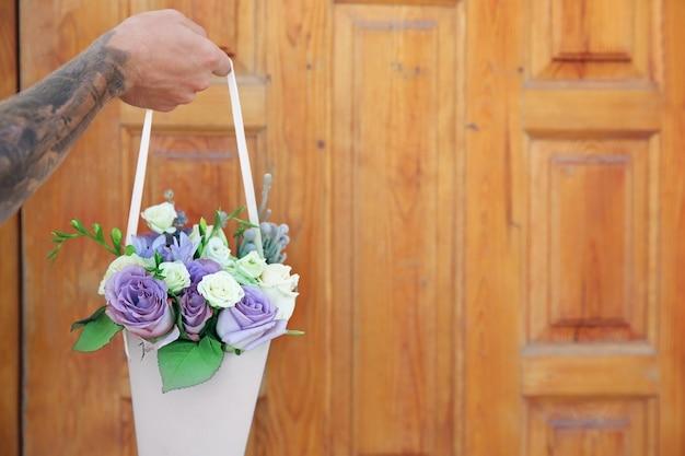 ドアの表面に美しい花束を持っている男性の手