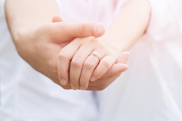 リングと美しい女性の手を握って男性の手