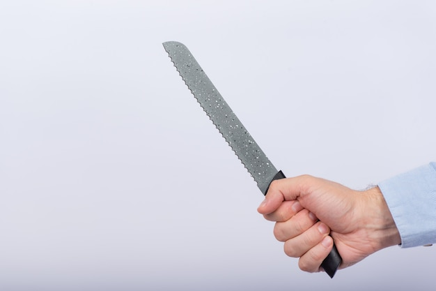 Male hand holding big knife on white background. bread knife in hand. close up. side view
