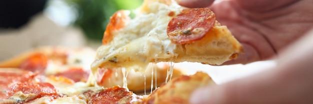 맛있는 신선한 피자의 큰 조각을 들고 남자 손