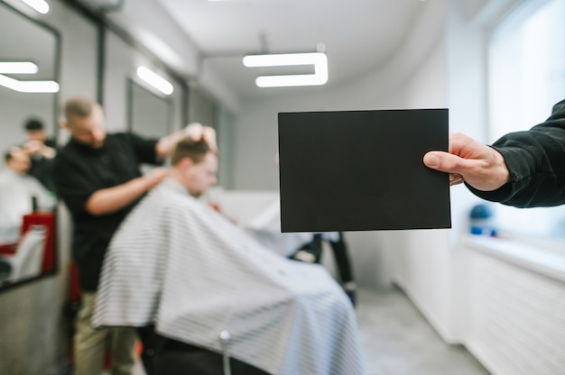 Male hand holding blank black card for copyspace on background of male hairdresser and barber clipping clients.