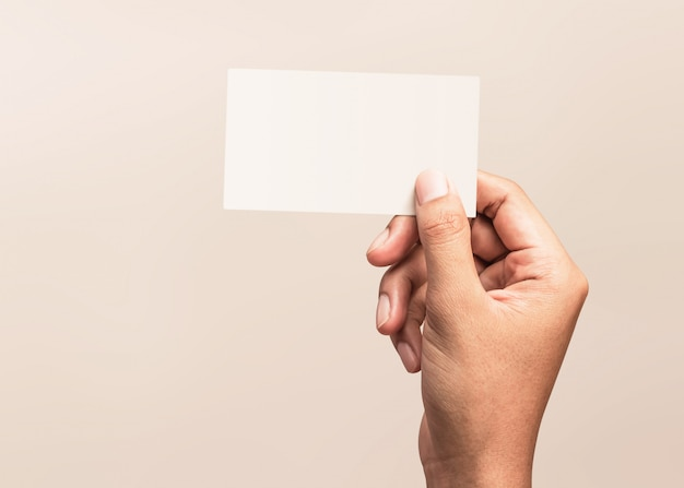 Male hand holding a blank business card on a gray background for text or design