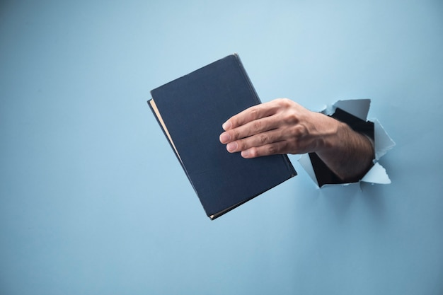 Male hand holding a book on a blue scene