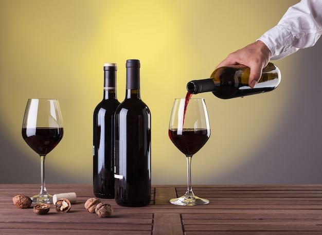 赤ワインのボトルを持って、ワイングラスに注ぐ男性の手