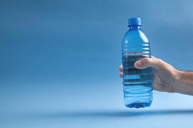 青い背景に水のボトルを持っている男性の手。