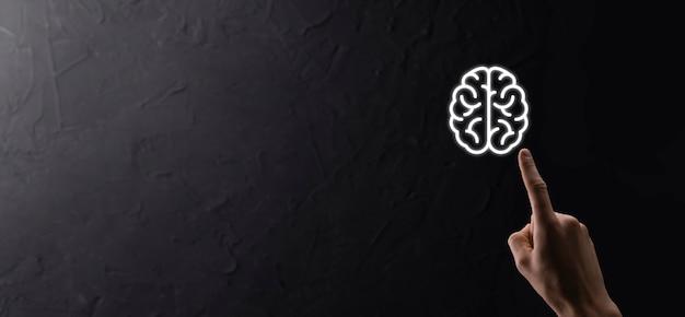 Мужская рука, держащая значок мозга на синем фоне. искусственный интеллект машинного обучения бизнес-концепция интернет-технологий. баннер с копией пространства