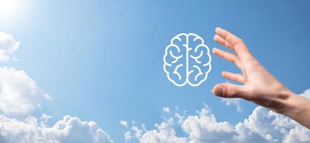 青の背景に脳のアイコンを持っている男性の手。人工知能機械学習ビジネス インターネット技術コンセプト。コピー スペースを持つバナー。