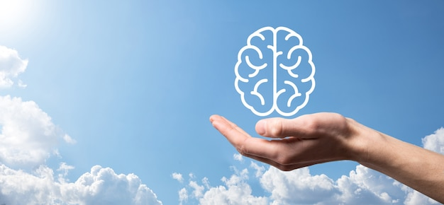 Мужская рука, держащая значок мозга на синем фоне. искусственный интеллект машинное обучение бизнес-концепция интернет-технологий. баннер с копией пространства.