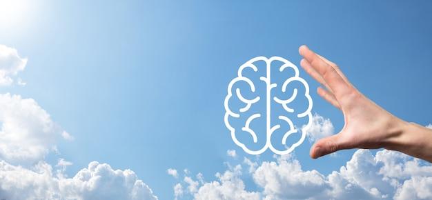 Мужская рука, держащая значок мозга на синей поверхности