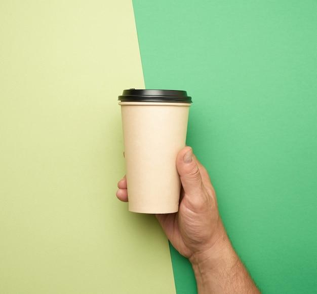 Мужская рука, держащая одноразовый стаканчик из коричневой бумаги