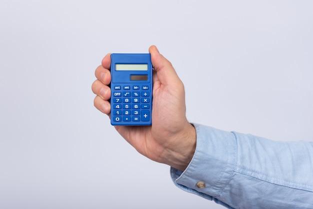 白の電卓を持っている男性の手。金融活動。会計。