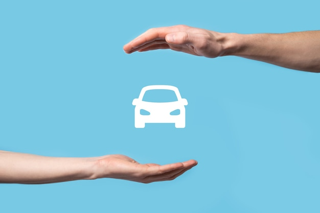 Male hand holding car auto icon on blue background. wide banner composition.car automobile insurance and collision damage waiver concepts.