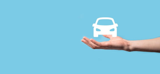 Male hand holding car auto icon on blue background. wide banner composition.