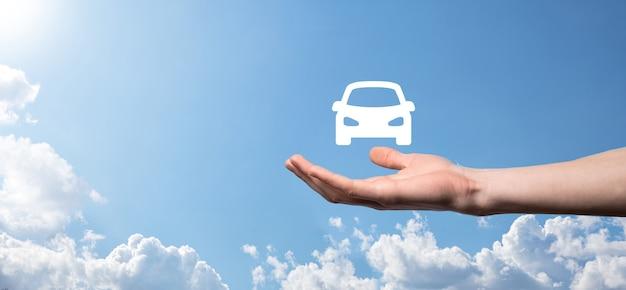 青い背景に車の自動アイコンを持っている男性の手。広いバナー構成。自動車保険と衝突被害免除の概念