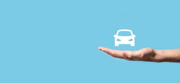 青い背景の上の車の自動アイコンを持っている男性の手