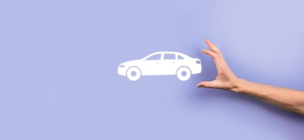 灰色の背景に車の自動アイコンを持っている男性の手。広いバナー構成。自動車保険と衝突被害免除の概念