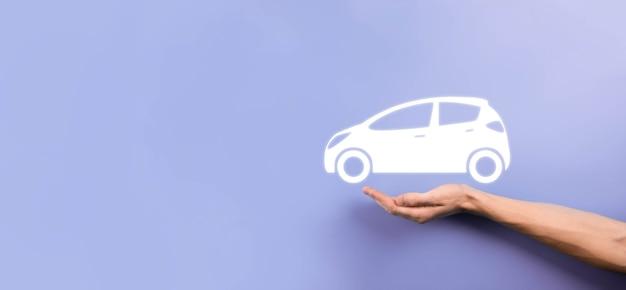 회색 배경에 자동차 자동 아이콘을 들고 있는 남성 손. 넓은 배너 구성입니다.자동차 자동차 보험 및 충돌 피해 면제 개념입니다.