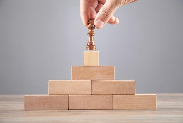 木製のブロックにチェスの駒を持っている男性の手。