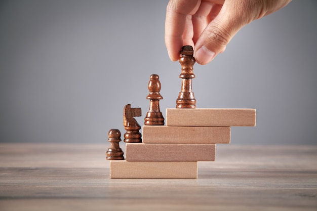 Male hand holding chess piece on wooden blocks.