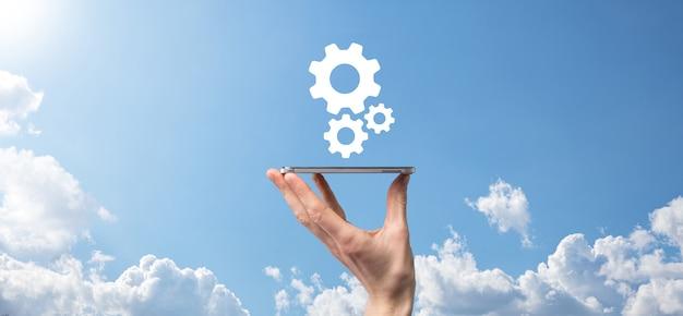 파란색 배경의 가상 화면에 톱니바퀴 아이콘, 메커니즘 아이콘을 들고 있는 남성 손. 자동화 소프트웨어 기술 프로세스 시스템 비즈니스 개념입니다. 배너