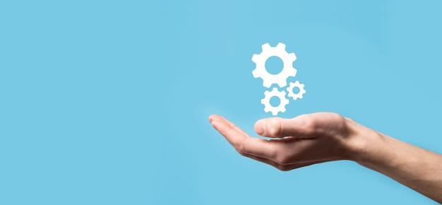 歯車のアイコン、青い背景の仮想画面上のメカニズムのアイコンを持っている男性の手。自動化ソフトウェア技術プロセスシステムビジネスコンセプト。バナー。