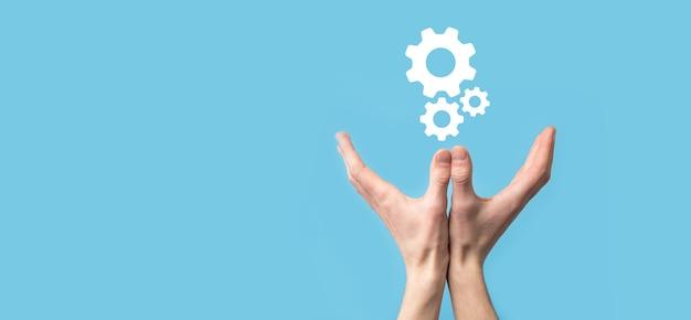 남자 손을 잡고 장부 기어 아이콘, 파란색 배경에 가상 화면의 메커니즘 아이콘. 자동화 소프트웨어 기술 프로세스 시스템 비즈니스 개념. 배너.