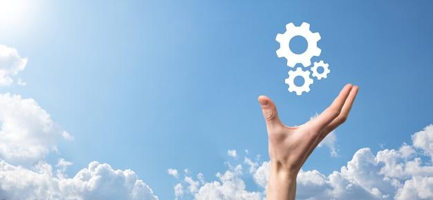 歯車のアイコン、青い背景の仮想画面上のメカニズムのアイコンを持っている男性の手。自動化ソフトウェア技術プロセスシステムビジネスコンセプト。バナー
