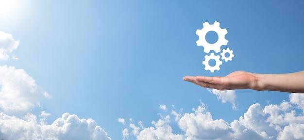 파란색 배경의 가상 화면에 톱니바퀴 아이콘, 메커니즘 아이콘을 들고 있는 남성 손. 자동화 소프트웨어 기술 프로세스 시스템 비즈니스 개념입니다. 배너.