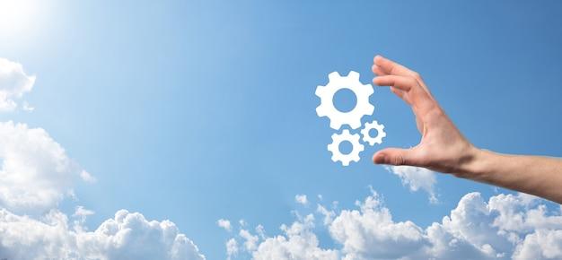 Мужская рука, держащая значок шестеренок, значок механизма на виртуальных экранах на синем фоне. система процессов автоматизации программного обеспечения бизнес-концепция. баннер
