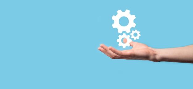 歯車のアイコン、青い背景の仮想画面上のメカニズムのアイコンを持っている男性の手。自動化ソフトウェア技術プロセスシステムビジネスコンセプト。
