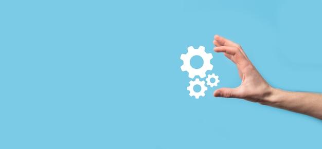 歯車のアイコン、青い表面の仮想画面上のメカニズムのアイコンを持っている男性の手