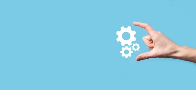남자 손을 잡고 톱니 기어 아이콘, 파란색 표면에 가상 화면의 메커니즘 아이콘