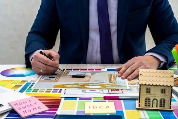 インテリアの視点で色のサンプルを持っている男性の手。アパートのスケッチ、素材、色のサンプルを扱うインテリアデザイナーの手