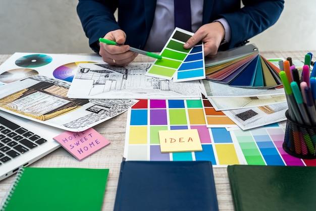 내부 관점으로 색상 샘플을 들고 남성 손입니다. 아파트 스케치, 재료 및 색상 샘플로 작업하는 인테리어 디자이너의 손