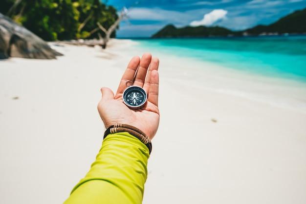 열 대 모래 해변과 바다에 나침반을 들고 남성 손. pov 여행 휴가 모험 개념.