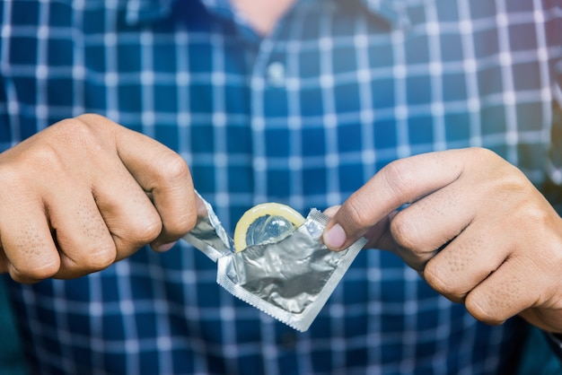 Male hand holding condom. safe sex concept.